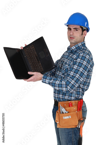 Tradesman looking at the underside of his laptop