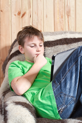 boy teenager with tablet computer sitting in chair