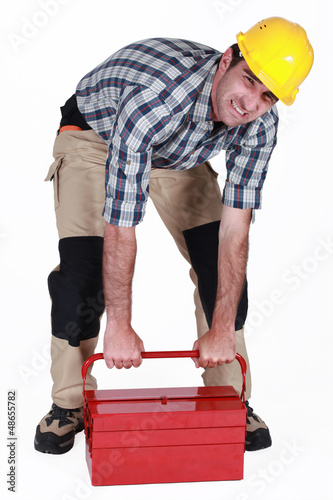 Builder struggling to lift heavy tool box
