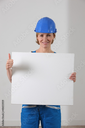 Woman in a hard hat with a blank board and the thumbs up