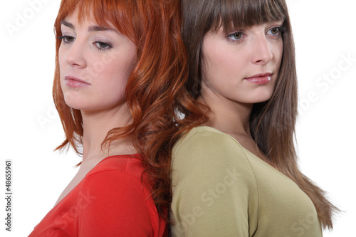 Two female friends stood back to back