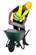 craftsman putting stones in a wheelbarrow