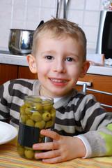 Niño comiendo aceitunas en la cocina.