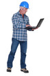 middle aged craftsman standing with laptop
