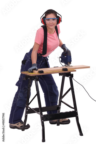 Woman cutting plank of wood with band saw