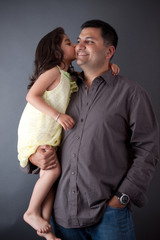 An East Indian girl kisses her father