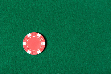 Top view of red poker chip on the green table