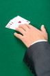 Hand with aces on the green table