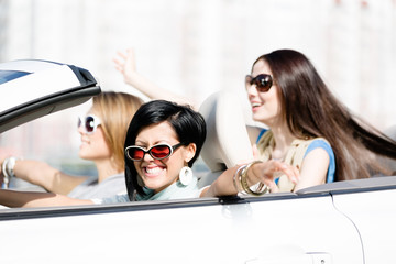 Group of happy girls in the white car