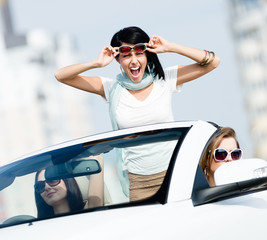 Lovely teenager stands in the car with friends