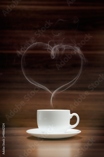 Cup of coffee with heart-shaped smoke on dark wood background