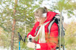 Woman wearing sport red jacket in winter forest.