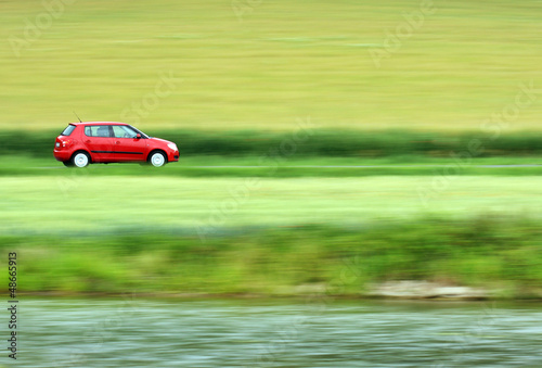 Panning shot of a fast moving red small car
