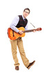 Full length portrait of a young male playing a guitar
