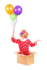 Male clown in a cardboard box holding bunch of balloons