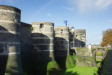 Towers and bridge of castle of Angers under rainbow, France and