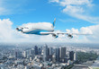 White passenger plane flying above a city