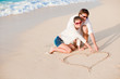 portrait of young happy couple drawing a heart on the sand