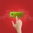 love button with real hand on red background