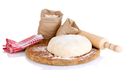 Dough and bags with flour on wooden board isolated on white