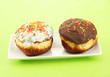 Tasty donuts on color plate on color background