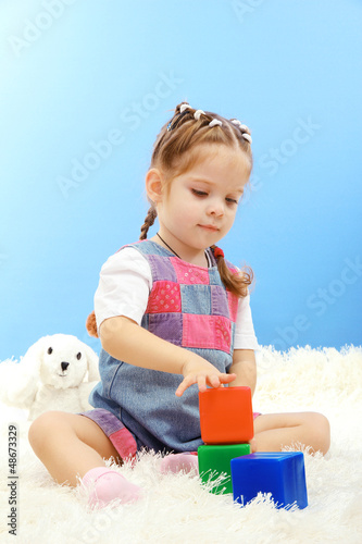 cute little girl playing with multicolor blocks,