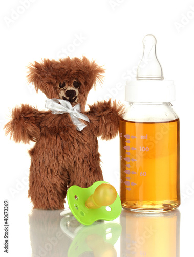 Baby bottle with fresh juice and teddy bear isolated on white