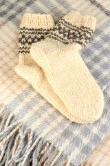 Warm knitted socks on plaid close-up