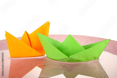 Color paper ship in water on pink plate, close-up - 48673557