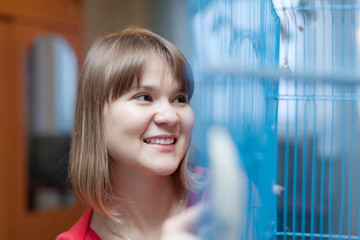 Smiling woman at the cage with pets