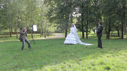 marrying couple on a swing. Photographing process in park