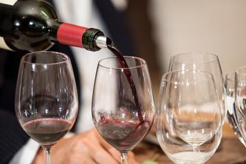 Mozo sirviendo vino en copas.