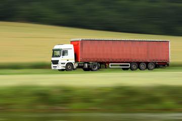 large red truck speeding on highway