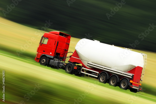 large white cistern truck speeding on highway