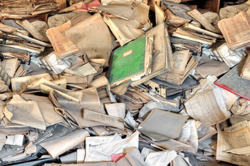 Pile of old yellowed documents in an abandoned building