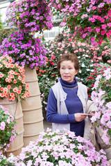 花に囲まれた高齢者の女性