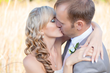 Happy young bride and groom kissing in grass on wedding day