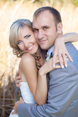 Happy young bride and groom hugging in grass in wedding day