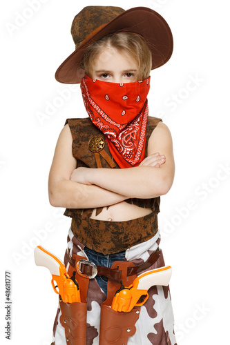 Little serious girl cowboy standing with folded hands