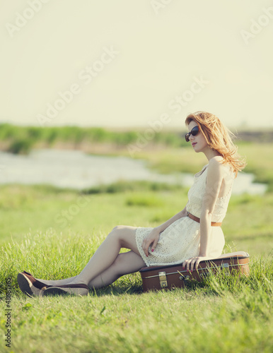 Young fashion girl with suitcase sitting at spring grass near la