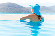 Woman in hat relaxing at swimming pool