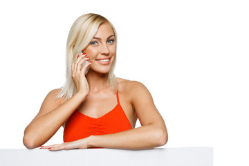 Smiling woman leaning on whiteboard talking on cellphone