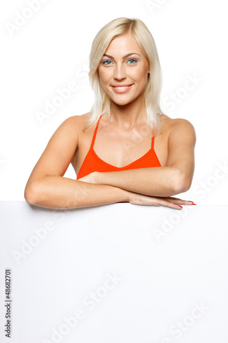 Smiling woman standing behind and leaning on white billboard