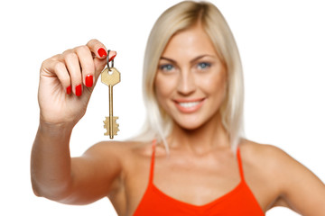 Closeup of pretty young lady giving you a key, focus on key