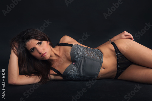 Sexy woman portrait wearing top corset and lying down