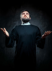 Portrait of priest against dark background