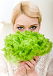 Portrait of beautiful blond woman hiding behind lettuce