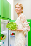 Smiling young woman taking vegetables out of fridge