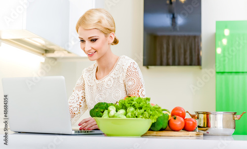 Woman looking for a recipe on the computer in the kitchen