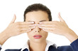 Attractive businesswoman covering her eyes